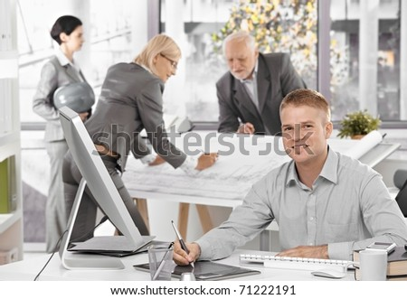 Architects busy at work, young designer in focus sitting at desk using drawing pad, smiling at camera.? - stock photo