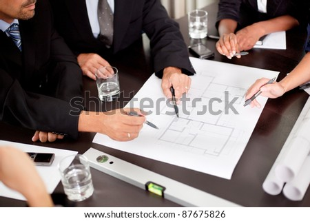 Architects discussing at the table with blueprint - Closeup on hands and project print - stock photo