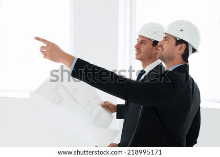 Architects in helmets indoor - stock photo