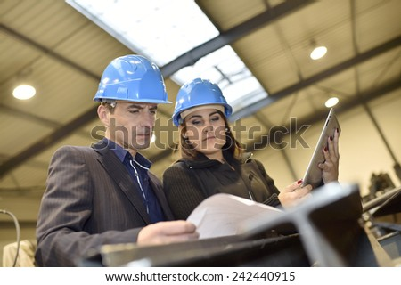 Architects in industrial workshop checking on project - stock photo