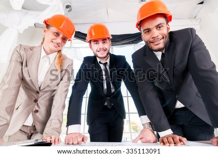 Architects of the drawings. Three businessm�µn architect met in the office to discuss business projects. Successful young people in the construction helmets are on the table
