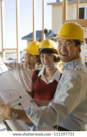 Architects reviewing blueprint at construction site - stock photo