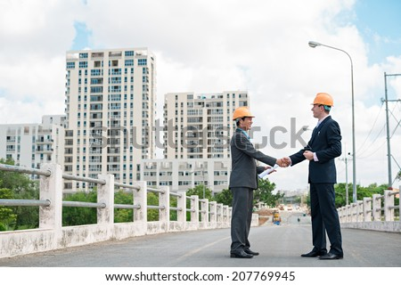 Architects shaking hands on the background of new district - stock photo