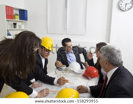 architects sitting at table and looking at a project - stock photo