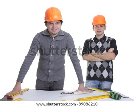 Architects standing over blueprints