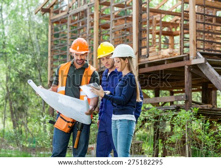 Architects using digital tablet together while analyzing blueprint at construction site - stock photo