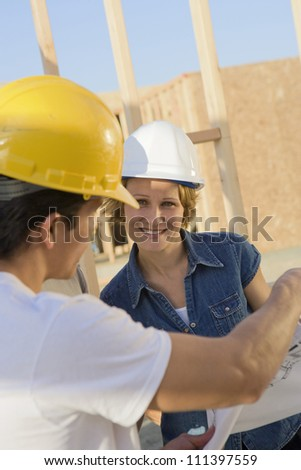 Architects with blueprint discussing at construction site - stock photo