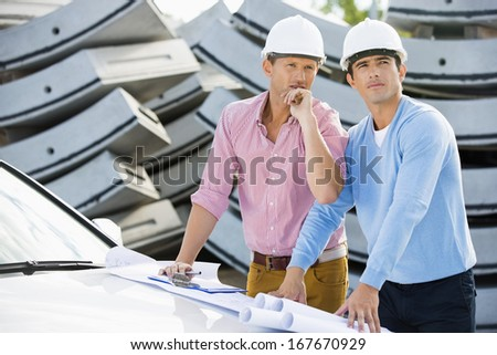 Architects with blueprints on car inspecting site - stock photo