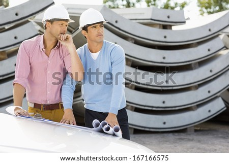 Architects with blueprints on car working at construction site - stock photo