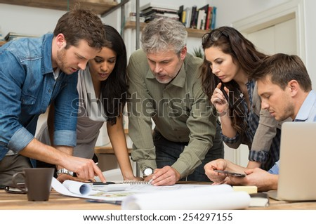 Architects working and discussing on blueprints at office