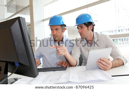 Architects working on construction plan - stock photo