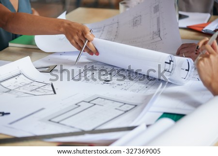 Architects working on plans at business boardroom table - stock photo