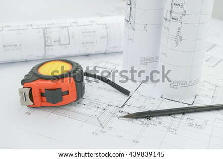 architects workplace - architectural blueprints with measuring tape and black pencil on table. - stock photo