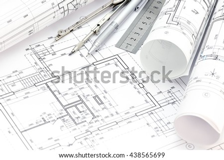 architectural background with plan, blueprints rolls and drawing tools - stock photo