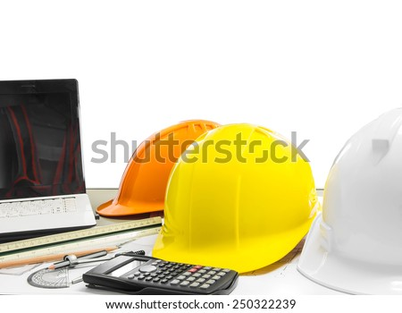 Architectural blueprint of office building with safety helmet , stationery , notebook
