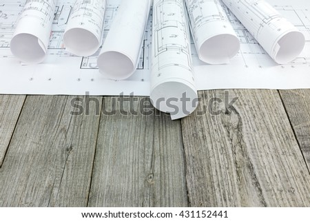 architectural blueprint rolls and floor plan drawing on gray wooden background - stock photo