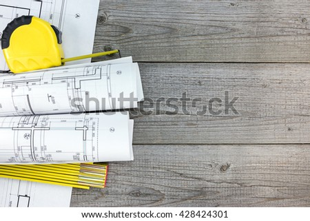 architectural blueprint rolls with tape measure and folding rule on wooden table  - stock photo
