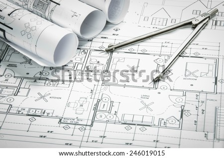 Architectural blueprints and blueprint rolls and a drawing instruments on the worktable - stock photo