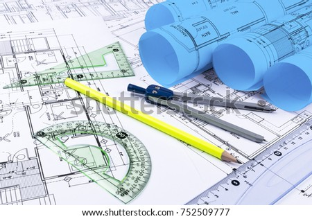 Architectural blueprints blueprint rolls drawing instruments stock architectural blueprints and blueprint rolls and a drawing instruments on the worktable drawing compass malvernweather Choice Image