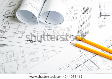 Architectural blueprints and blueprint rolls and two yellow pencils - stock photo