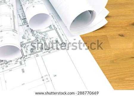 architectural blueprints and blueprint rolls on wooden table - stock photo