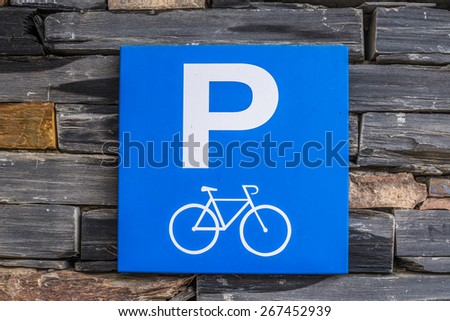 Architectural brick stone wall with parking sign for bicycle Blue parking sign for bikes on a colorful wall built with natural brick stones for background pattern - stock photo