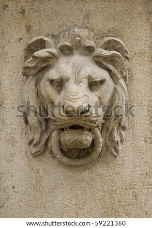 Architectural detail of a lion's head on the wall of a building