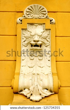 Architectural detail of a lion's head on the yellow wall of a building - stock photo