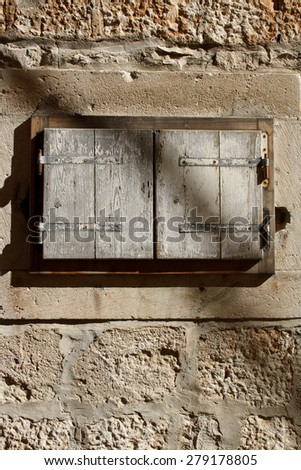 Architectural detail: small rustic window on a traditional Mediterranean house. Vertical format, natural light.