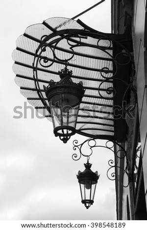 Architectural detail. Typical French canopy with two vintage lanterns at door entrance. Black and white photo. - stock photo