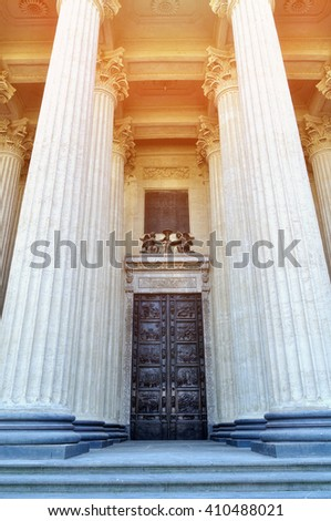 Architectural details of Kazan Cathedral  in Saint-Petersburg, Russia - bronze doors and tall columns under warm sunlight.