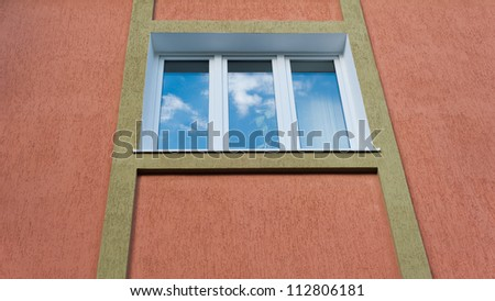 architectural details. one window  with a brown stucco.