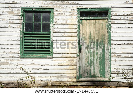 Architectural Details show peeling paint and an old window and door - stock photo