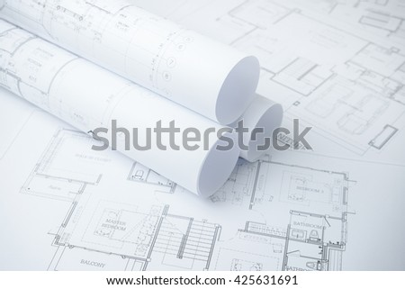 architectural drawing paper rolls of a dwelling for construction - stock photo