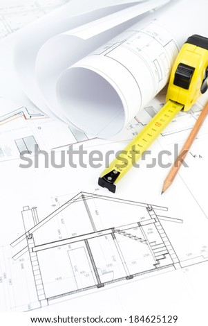 Architectural drawings, rolls of blueprints with tape measure and pencil - stock photo