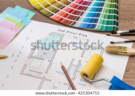 architectural drawings with color guide, paint roller, brushes, pencil