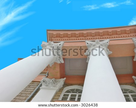 Architectural element of a building in antique style on a background of the clear blue sky. Very light, vital photo. - stock photo