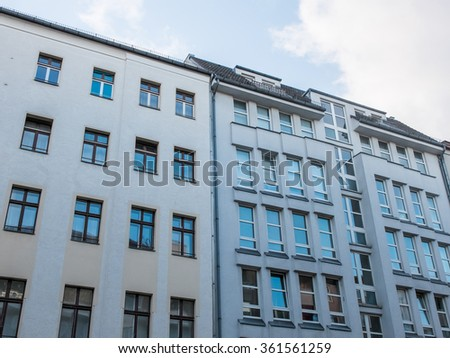 Architectural Exterior Close Up Contrasting Old and New Residential Apartment Buildings in Urban Environment with Blue Sky and Clouds in Background