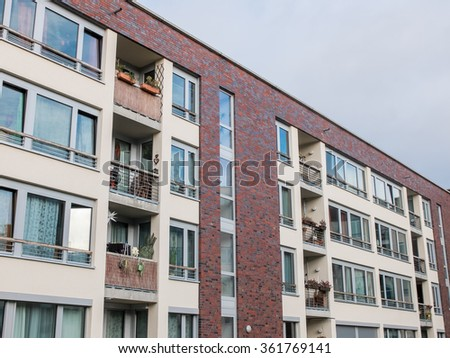 Architectural Exterior Detail Of Brick Residential Apartment Building With  Small Balconies And Framed By Overcast Sky