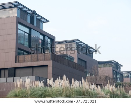 Architectural Exterior Detail of Modern Modular Homes with Rear Patios and Surrounded by Lush Plant Vegetation on Hazy Day - stock photo