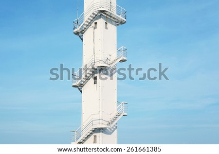 Architectural fragment of the white tower with a metal spiral staircase against the blue sky - stock photo