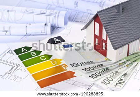 Architectural model, architectural plans, energy efficiency labels and money. - stock photo