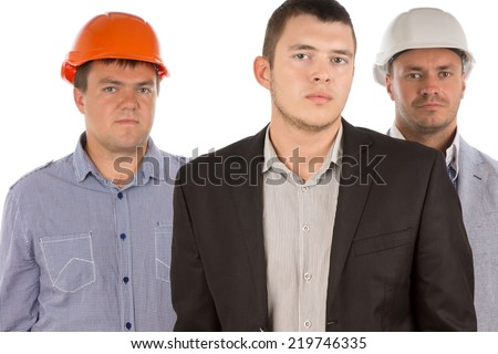 Architectural or building team with a young man in a suit flanked by two older men in hardhats all standing looking at the camera with serious expressions, isolated on white - stock photo