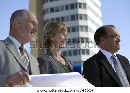 Architectural planning team of three with plans, on location in front of a building - stock photo