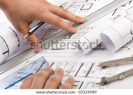 Architectural plans and blueprints in office - stock photo