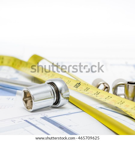 Architectural plans with tools on white background.