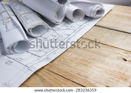 Architectural project, blueprints, blueprint rolls on vintage wooden background. Construction concept. Engineering tools top view. Copy space - stock photo