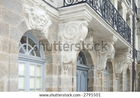 Architectural sculptures - mascarons - on the facade of a 18th century building in Nantes, France. Black wrought iron balcony and corbels on tuffeau stone facade. - stock photo