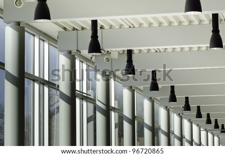 Architectural symmetry: Interior view of columns, windows, and light fixtures along hallway of state university - stock photo