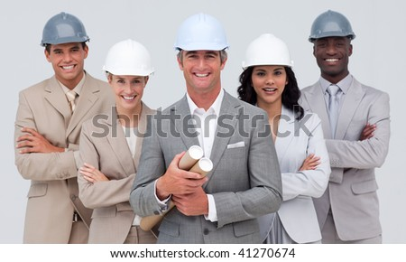 Architectural team smiling at the camera with hard hats and holding blueprints - stock photo